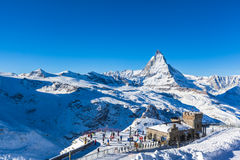 Matterhorn and Gornergratbahn. Zermatt, Switzerland - December 31, 2014 -The train station at Gonergrat with clear view to Matterhorn. People strats to ski from stock images
