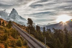 Matterhorn peak with railway with sunset in Swiss Alps, Switzerland. Matterhorn peak with railway against sunset in Swiss Alps, Switzerland royalty free stock images