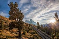 Matterhorn peak with railway against sunset in Swiss Alps, Switzerland. Famous Matterhorn peak with railway against sunset in Swiss Alps, Switzerland stock image