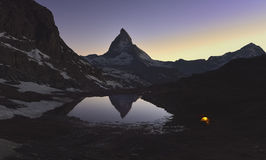 Matterhorn peak reflected in the Riffelsee with a lighted tent Royalty Free Stock Photos