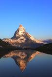 Matterhorn peak and reflection. On Riffelsee in reddish sunlight of early morning, Switzerland Stock Photo