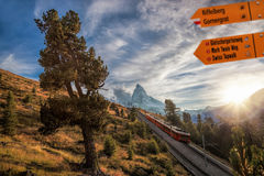 Matterhorn peak with Signpost against train in Swiss Alps. Famous Matterhorn peak with Signpost against train in Swiss Alps stock photography