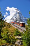 Matterhorn with railroad and train. Mountain train in front of Matterhorn peak royalty free stock image