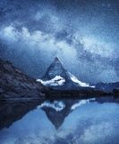Matterhorn and reflection on the water surface at the night time. Milky way above Matterhorn, Switzerland. Beautiful natural landscape in the Switzerland stock image