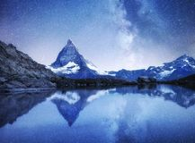Matterhorn and reflection on the water surface at the night time. Milky way above Matterhorn, Switzerland. stock photo