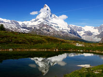 Matterhorn reflects in mountain. Famous mountain Matterhorn on a beautiful summer day reflects in the water of a mountain lake royalty free stock photo