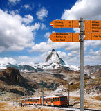 Matterhorn with Signpost against train in Swiss Alps. Famous Matterhorn with Signpost against train in Swiss Alps stock images