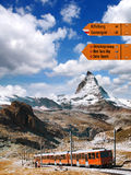 Matterhorn with Signpost against train in Swiss Alps. Famous Matterhorn with Signpost against train in Swiss Alps royalty free stock photo