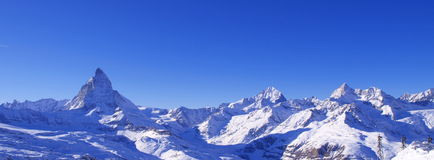 Matterhorn and Swiss Alps Panorama. A panorama of the Matterhorn and the surrounding mountain peaks. A streaking star crosses the sky now and then Stock Photos