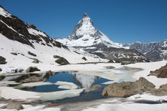 Matterhorn view. Classic view on the Matterhorn with the partly frozen Riffelsee in the foreground Royalty Free Stock Photo
