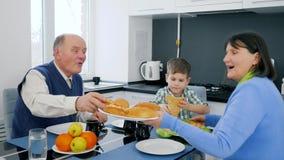 Mattid, farmor kom med läckra bageriprodukter på plattan för pojke- och farfarsammanträde på skrivbordet lager videofilmer