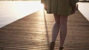 Mattina blu Metraggio della parte di una ragazza snella sull'talloni ed abito che cammina dal pilastro di legno seaside archivi video