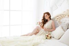 Mattina del ` s della sposa del boudoir Ragazza dai capelli rossi sveglia nel suo giorno delle nozze immagini stock libere da diritti