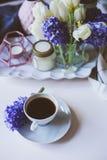 mattina della molla a casa con la tazza di caffè, le candele ed i fiori sulla tavola bianca Fotografia Stock Libera da Diritti