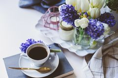 mattina della molla a casa con la tazza di caffè, le candele ed i fiori sulla tavola bianca Fotografia Stock