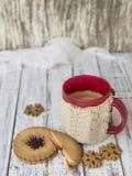Mattina di inverno, tazza di caffè con i supporti di tazza tricottati, pan di zenzero e biscotti della vaniglia su un fondo di le fotografia stock