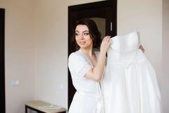 Mattina di nozze: bella sposa che prova su un vestito da sposa Fotografia Stock Libera da Diritti