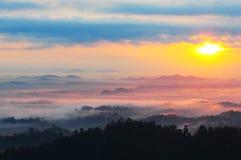 Mattina nebbiosa alla collina di panorama. Immagine Stock