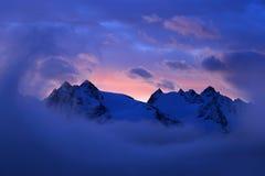 Mattina nebbiosa in alpi italiane, primo mattino nella montagna con neve durante la penombra viola, colline nelle nuvole Fotografie Stock Libere da Diritti