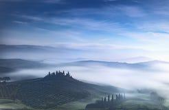 Mattina nebbiosa blu della Toscana, terreno coltivabile ed alberi di cipresso L'Italia Fotografie Stock Libere da Diritti