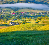 Mattina nebbiosa di estate in paesino di montagna fotografie stock