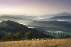 Mattina nebbiosa scenica nel paesaggio delle montagne Fotografia Stock