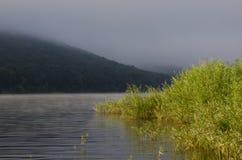 Mattina nebbiosa sopra la baia contro lo sfondo di una montagna immagini stock