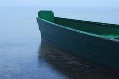 Mattina nebbiosa sul lago Barca verde attraccata alla riva Fotografie Stock Libere da Diritti