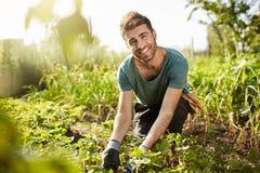 Mattina rurale Chiuda su di bello agricoltore maschio caucasico barbuto in maglietta blu e pantaloni neri che sorride, lavorando  Fotografia Stock Libera da Diritti