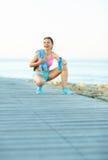 Mattina soleggiata sulla spiaggia, donna atletica che riposa dopo avere corso Fotografia Stock Libera da Diritti