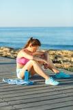 Mattina soleggiata sulla spiaggia, donna atletica che riposa dopo avere corso Immagine Stock Libera da Diritti
