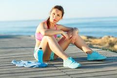 Mattina soleggiata sulla spiaggia, donna atletica che riposa dopo avere corso Fotografia Stock
