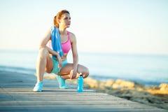 Mattina soleggiata sulla spiaggia, donna atletica che riposa dopo avere corso Fotografie Stock