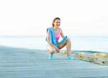Mattina soleggiata sulla spiaggia, donna atletica che riposa dopo avere corso Immagine Stock