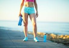 Mattina soleggiata sulla spiaggia, donna atletica che riposa dopo avere corso Fotografie Stock Libere da Diritti