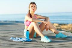 Mattina soleggiata sulla spiaggia, donna atletica che riposa dopo avere corso Immagini Stock