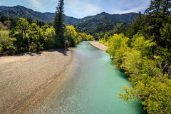 Mattole River flows along at the edge of the forest with turquoise water and pebble beach Stock Photos