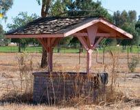 Mattone decorativo che desidera bene con il tetto coperto assicella immagine stock