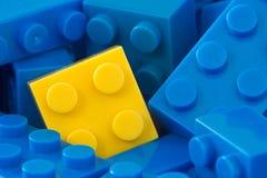 Mattone di plastica giallo in una metà dell'azzurro un Fotografia Stock