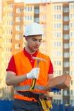 Mattone e martello della maglia del costruttore e della tenuta del cantiere del casco in mani immagine stock libera da diritti