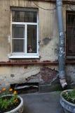 Mattone, gesso, sbucciando parete con una finestra e un tubo di scarico Fotografia Stock