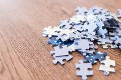 mattonelle blu di un puzzle su una tavola di legno Concetto per indicare le Immagini Stock Libere da Diritti