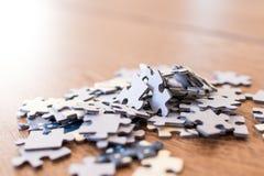 mattonelle blu di un puzzle su una tavola di legno Concetto per indicare le Fotografie Stock Libere da Diritti