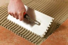 Mattonelle della piastrellatura del piastrellista sul pavimento Immagini Stock