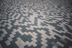 Mattonelle di pavimentazione modellate grige e bianche sul terreno della via, vista di prospettiva Il mattone del cemento ha quad immagine stock