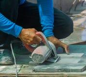 Mattonelle di taglio del lavoratore dell'uomo con la sega circolare Fotografia Stock