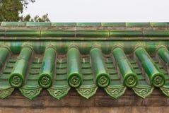 Mattonelle di tetto lustrate verde sulla parete immagini stock