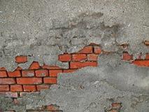 Mattoni che rivelano fuori da una parete del cemento immagine stock