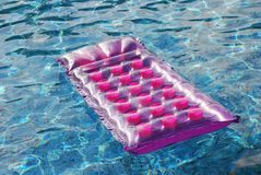 Mattress in pool. Pink air mattress in pool Royalty Free Stock Image