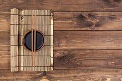 Mattt för sushi och pinnar på träbakgrund arkivbild